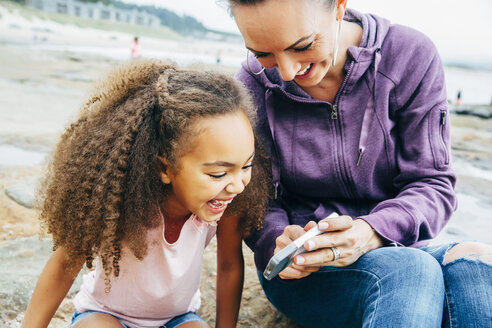 Mother and daughter using cell phone on beach - BLEF03963