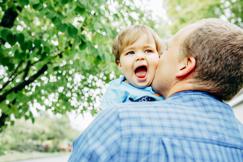 Father kissing cheek of baby son outdoors - BLEF03969