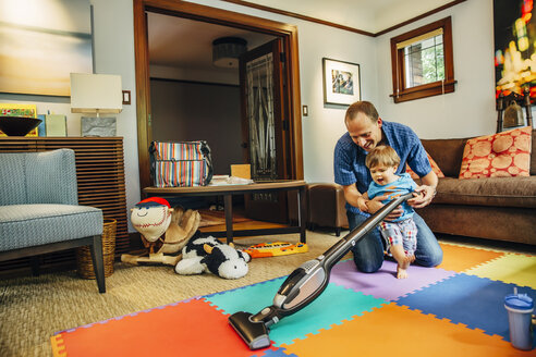 Father and son vacuuming living room - BLEF03972
