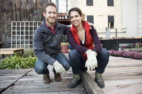 Couple smiling in urban rooftop garden - BLEF03993