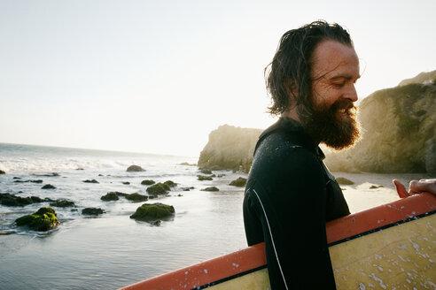 Caucasian man holding surfboard at beach - BLEF04032