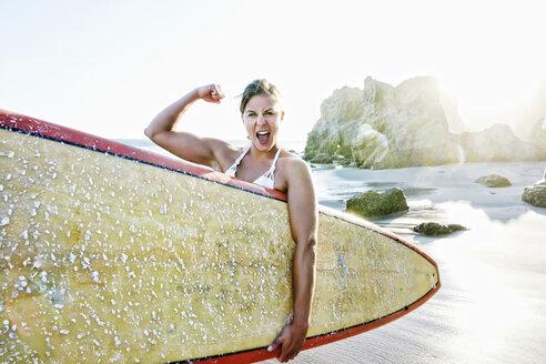 Caucasian surfer flexing muscle at beach - BLEF04035