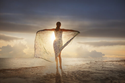 Caucasian woman holding fabric on beach at sunset - BLEF04059