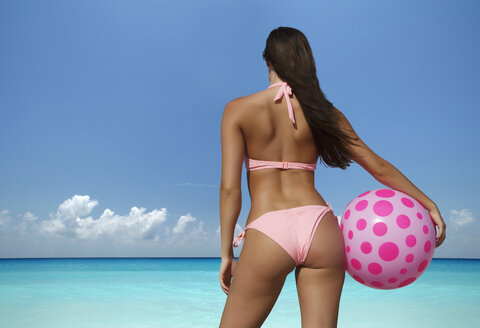Caucasian woman holding beach ball at ocean - BLEF04065