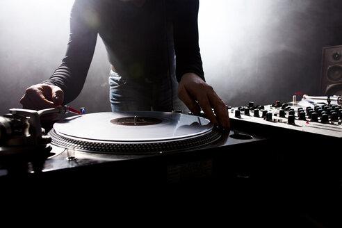 Caucasian disc jockey playing music in nightclub - BLEF04116