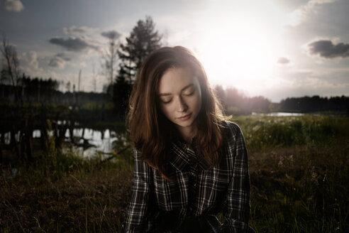Pensive Caucasian woman in field near lake - BLEF04332