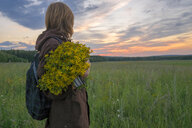Caucasian woman holding bouquet of flowers in field at sunset - BLEF04344