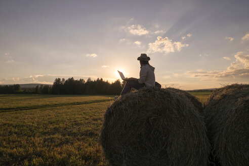 Mari man sitting on hay bale at sunset using laptop - BLEF04350