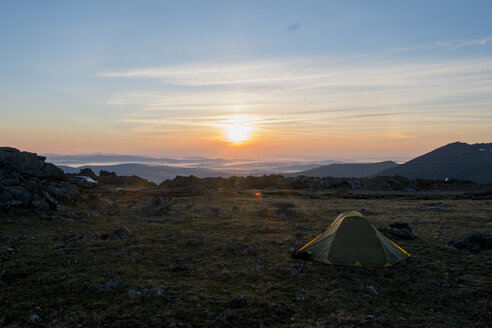 Camping tent in barren field at sunset - BLEF04422