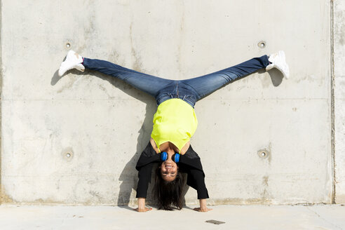 Woman with blue headphones listening music, making a handstand and split - ERRF01376