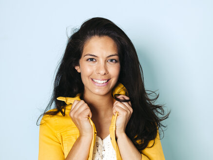 Portrait of young woman with black hair wearing yellow denim jacket, light blue background - HMEF00399