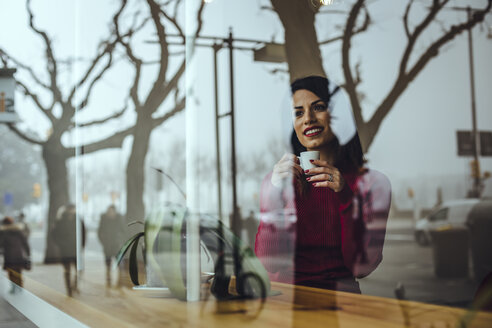 Smiling young woman with cup of coffee behind windowpane in a cafe - ACPF00510