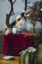 Portrait of beautiful young woman with cup of coffee behind windowpane in a cafe - ACPF00513
