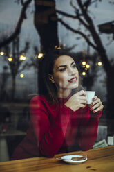 Smiling young woman with cup of coffee behind windowpane in a cafe - ACPF00516
