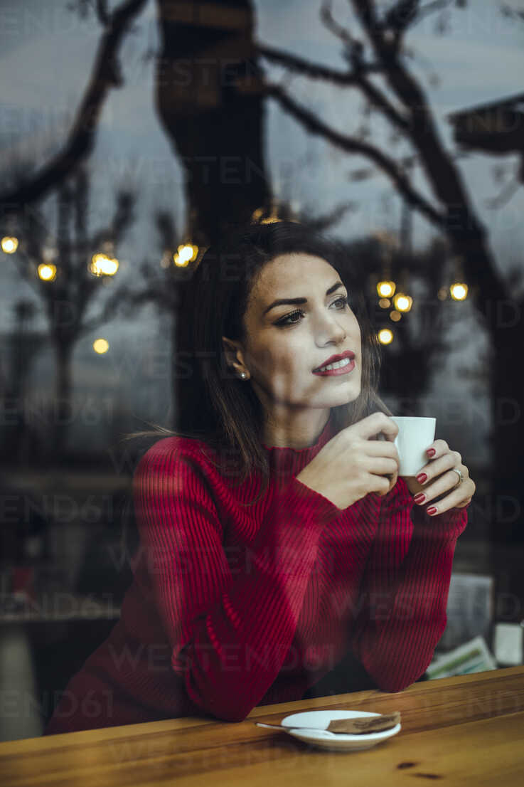 Smiling young woman with cup of coffee behind windowpane in a cafe - ACPF00516 - Aitor Carrera Porté/Westend61
