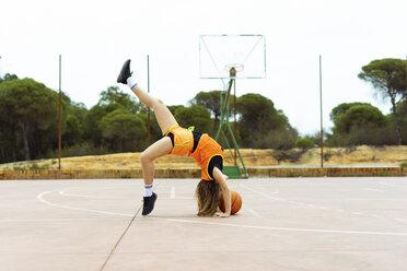 Teenage girl doing acrobatics on basketball ground - ERRF01383