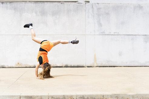 Teenage girl doing acrobatics outdoors - ERRF01386