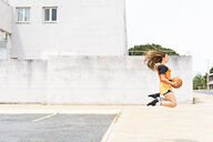 Teenage girl jumping with basketball outdoors - ERRF01389