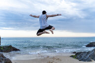 Back view of young man jumping in the air on the beach - AFVF03007