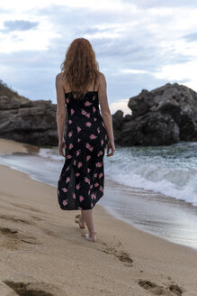 Back view of young woman wearing summer dress with floral design walkung on the beach - AFVF03016