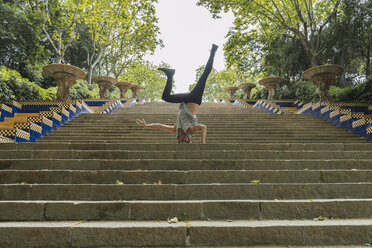 Young man doing acrobatics on stairs outdoors - AFVF03017