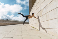 Young man doing acrobatics at a wall outdoors - AFVF03020