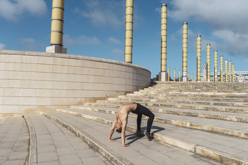Young man doing acrobatics on stairs outdoors - AFVF03026