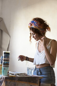 Young woman painting in art studio - JPTF00055