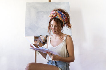 Young female painter in art studio next to empty canvas looking at papers - JPTF00061