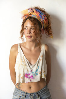Portrait of young artist standing in her studio looking sideways - JPTF00067