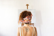Rear view of young female painter in art studio in front of empty canvas - JPTF00070