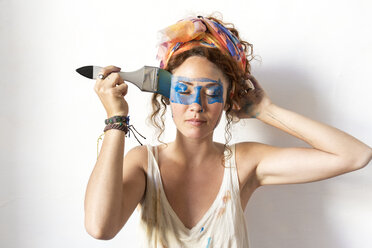 Portrait of a young woman painting with a brush on her face - JPTF00073