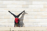 Teenage girl doing a handstand at a wall outdoors - ERRF01394
