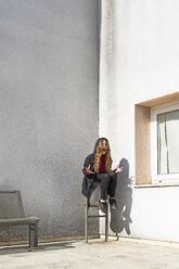 Screaming teenage girl sitting in a corner - ERRF01397