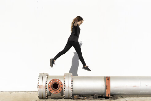 Teenage girl jumping over large pipe outdoors - ERRF01406