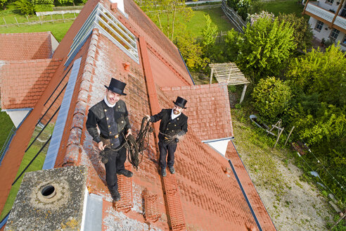 Portrait of two smiling chimney sweeps standing on house roof - MAEF12877