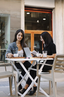 Two friends sitting together at a pavement cafe with book and laptop - OCAF00387
