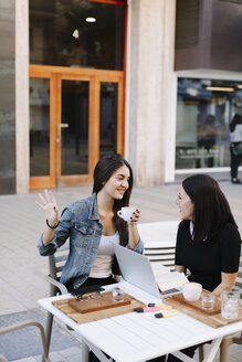 Two friends sitting together at a pavement cafe with laptop - OCAF00390