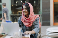 Smiling young woman with laptop wearing headscarf at a pavement cafe - OCAF00396