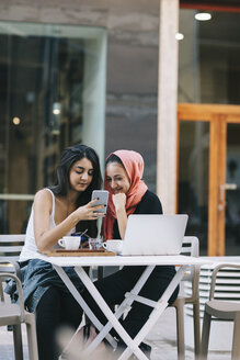 Two friends sitting together at a pavement cafe using cell phone - OCAF00405
