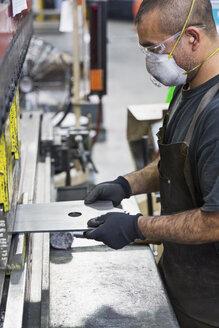 Hispanic worker wearing mask fabricating metal in factory - BLEF04453
