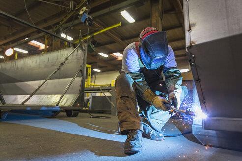 Caucasian man welding metal in factory - BLEF04459