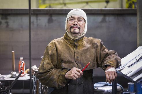 Smiling Asian worker wearing hood posing in factory - BLEF04462