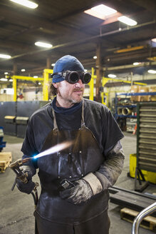 Caucasian welder holding blowtorch in factory - BLEF04471