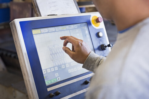 Asian worker using control panel in factory - BLEF04489