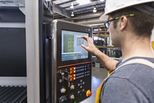 Caucasian worker using control panel in factory - BLEF04498