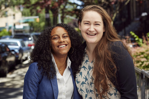 Laughing friends posing on city sidewalk - BLEF04513