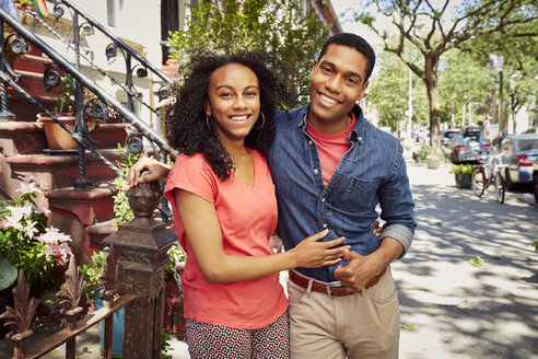 Smiling couple posing on city sidewalk - BLEF04516
