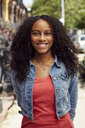 Smiling Mixed Race woman posing on city sidewalk - BLEF04519