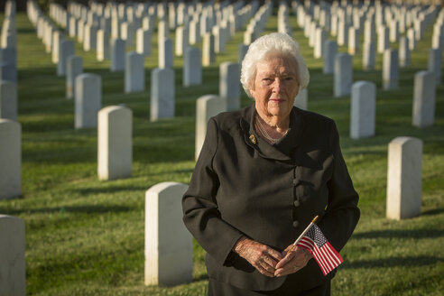 Caucasian widow holding American flag in cemetery - BLEF04525